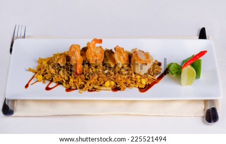 Mouth Watering Main Dish Lemony Risotto with Shrimps on Top. Prepared on White Rectangular Plate, Dine in White Table - stock photo