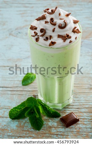 Mouthwatering milkshake with mint, milk and ice cream and near the glass. Chocolate as a decoration on the whipped topping on the top of the cocktail. Fresh taste for hot weather. - stock photo