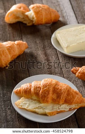 Mouthwatering shot of croissants from the oven. Bakery on white plate and on the wooden vintage table with butter. Traditional French specialty.