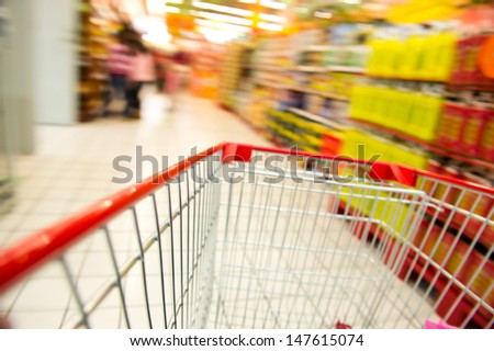move in the supermarket with shopping cart. - stock photo