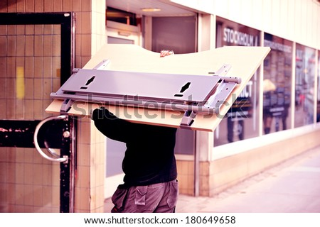 Mover carrying desk - stock photo