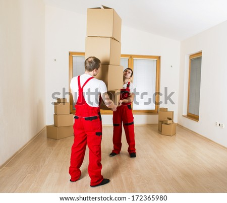Movers in new house with lot of boxes. - stock photo