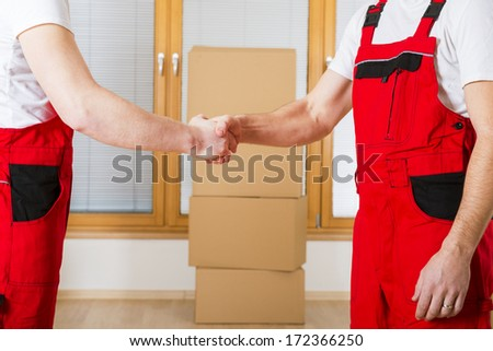 Movers in new house with lot of boxes behind them. - stock photo