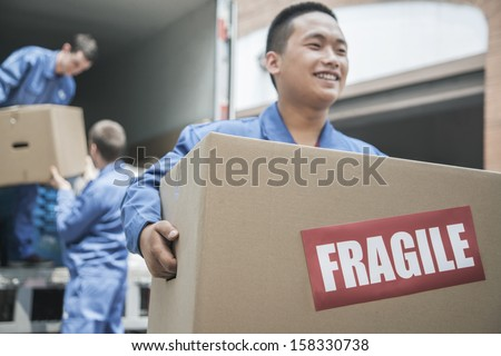 Movers unloading a moving van and carrying a fragile box - stock photo