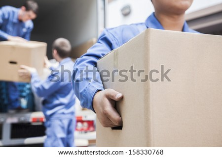 Movers unloading moving van - stock photo