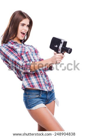 Movie camera as a weapon. Cheerful young woman holding movie camera while standing against white background - stock photo