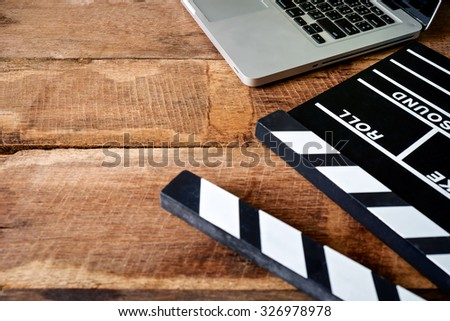 Movie clapper and laptop  on wooden background  - stock photo
