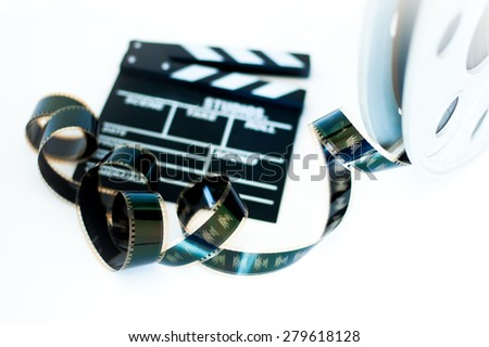 Movie clapper and vintage 35 mm film cinema reel on white background filmstrip selective focus - stock photo
