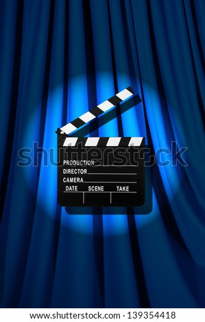 Movie clapper board against curtain - stock photo