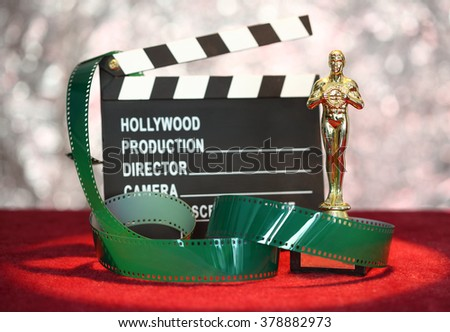 Movie clapper board and film roll in front glittering  background