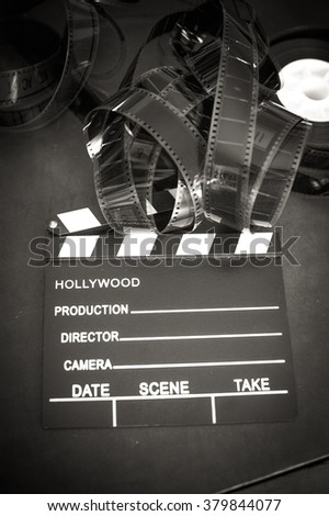 Movie clapper board and filmstrip selective focus and vintage black and white