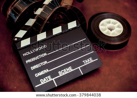 Movie clapper board and filmstrip selective focus and vintage color effect - stock photo