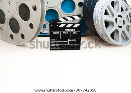 Movie clapper board and 35 mm cinema reels with film and blue box - stock photo