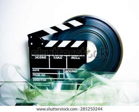 Movie clapper board and 35 mm film reel on white background vintage color effect - stock photo
