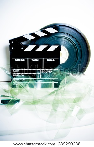 Movie clapper board and 35 mm film reel on white background vintage color effect vertical frame - stock photo