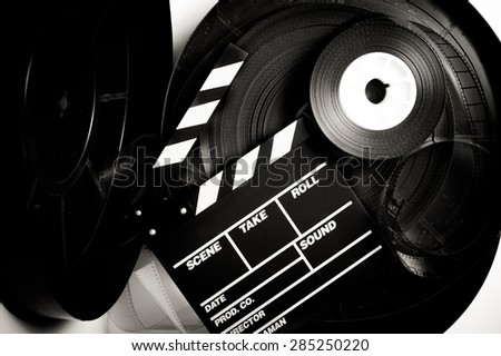 Movie clapper board on 35 mm movie reels in vintage black and white - stock photo