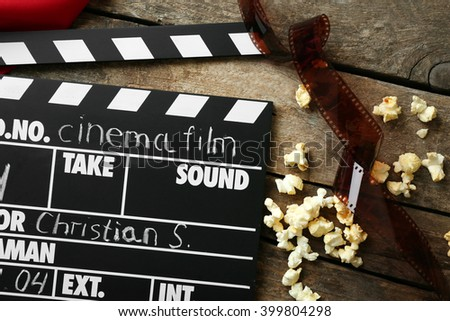 Movie clapper board with popcorn on the wooden table.
