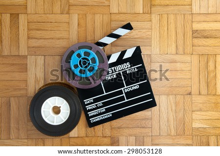 Movie clapper board with super 8 and 35 mm coloured film reels on wooden floor - stock photo
