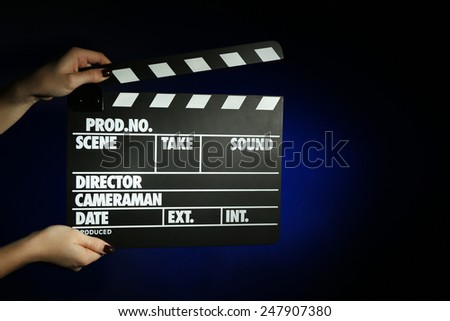 Movie clapper in female hand on dark color background - stock photo