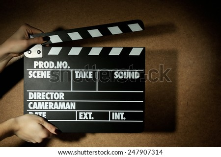 Movie clapper in female hand on wooden background - stock photo