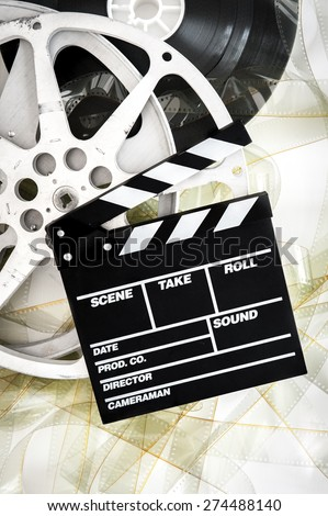 Movie clapper on 35 mm cinema reels unrolled filmstrip on white background vertical - stock photo