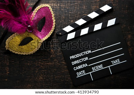 Movie clapper with carnival mask on dark background - stock photo