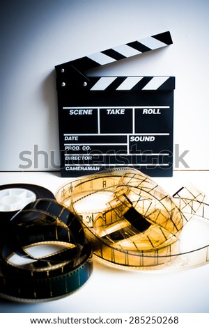 Movie clapper with 35 mm film on white background vertical frame vintage color effect - stock photo