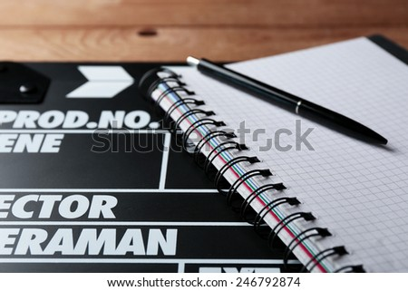 Movie clapper with notebook and pen on wooden background - stock photo