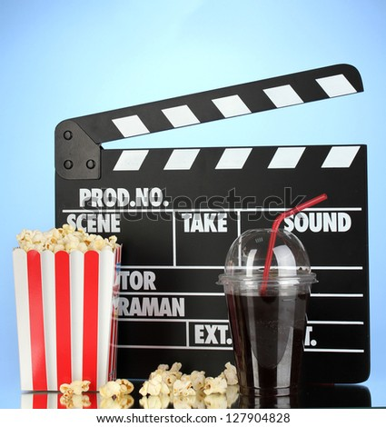 Movie clapperboard, cola and popcorn on blue background - stock photo
