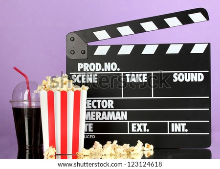 Movie clapperboard, cola and popcorn on purple background - stock photo
