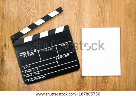 Movie production clapper board with empty paper against wooden background  - stock photo