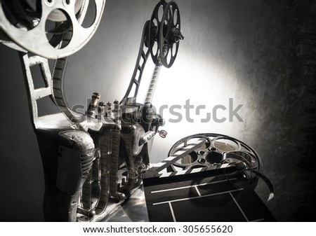 Movie projector with a film on the dark background - stock photo