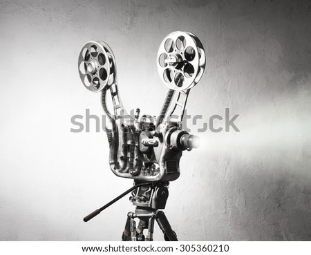 Movie projector with the film on the background of wall - stock photo