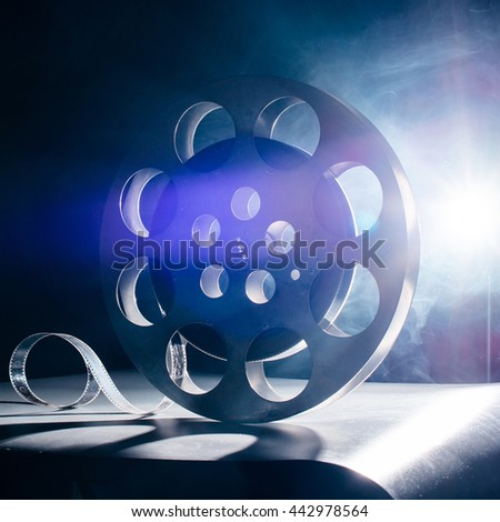 Movie reel of film in retro in the blue smoke on a dark background - stock photo