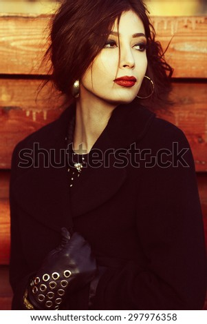 Movie star concept. Portrait of gorgeous fashionable young woman wearing luxurious clothing and golden accessories. Perfect hairdo and make-up. Elegant style. Cold autumn weather.  Outdoor shot