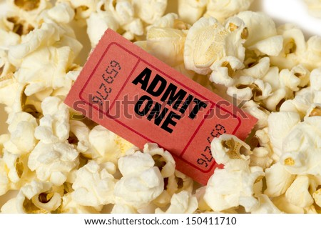 Movie Ticket In Center Of Popcorn/ Red Movie Ticket With Popcorn/ Close Up Of Popcorn With Ticket - stock photo