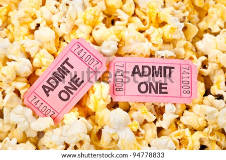 Movie tickets in a pool of freshly popped popcorn - stock photo