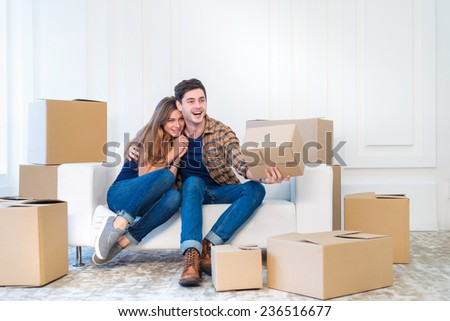 Moving and repair. Couple in love moving and keep a box in his hands and looking at the camera while a young and beautiful couple in love sitting on the couch in an empty apartment among boxes
