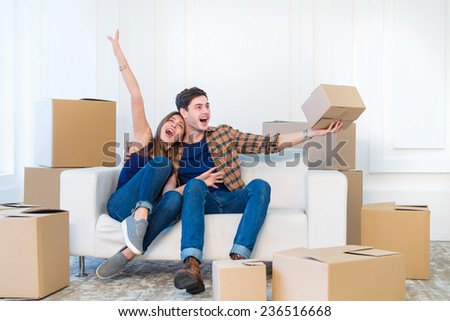 Moving and repair. Loving couple enjoys a new apartment and keep the box in his hands while young and beautiful couple in love sitting on the couch in an empty apartment among boxes - stock photo