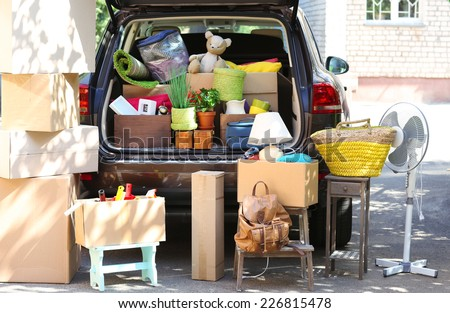 Moving boxes and suitcases in trunk of car, outdoors - stock photo