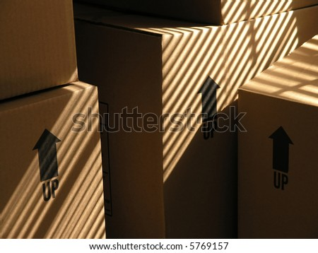 Moving boxes in dramatic window blind light - stock photo