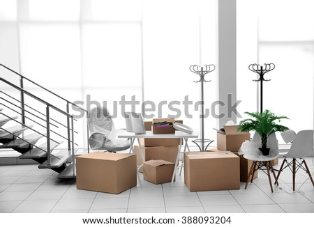 Moving cardboard boxes and personal belongings near stairs in office - stock photo