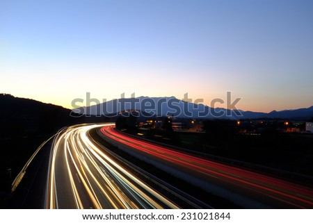 Moving cars leaving rays of colorful lights on busy highway at dusk. - stock photo