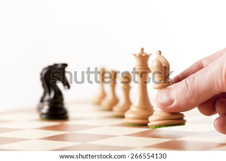 moving chess pieces on a chess board - stock photo