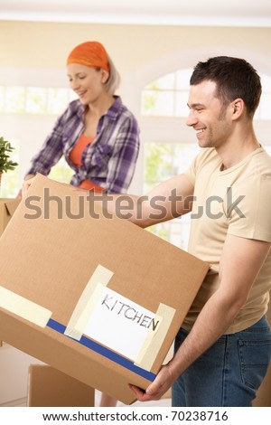 Moving couple carrying kitchen equipment boxes, smiling.?