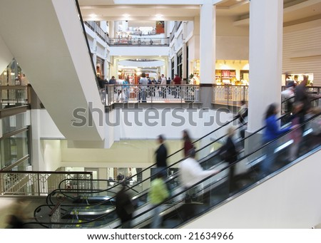 Moving crowd on escalator in shopping mall - stock photo