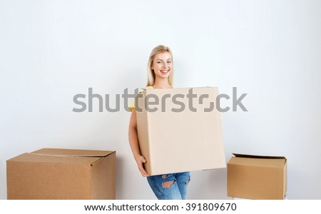 moving, delivery, housing, accommodation and people concept - smiling young woman with cardboard box at home - stock photo