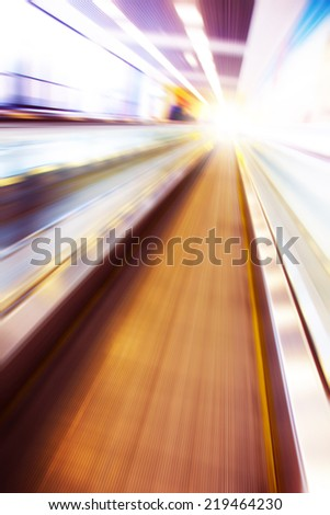 Moving escalator in modern building and light on background.