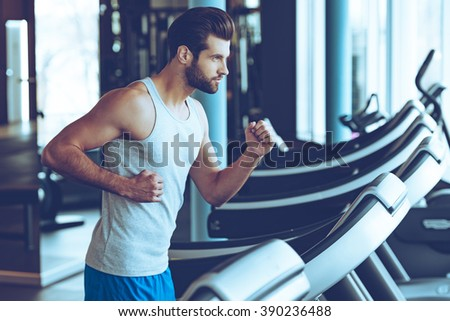 Moving fast. Side view of young man in sportswear running on treadmill at gym - stock photo