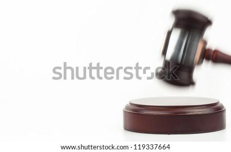 Moving gavel banging on the wood sound block on white background - stock photo